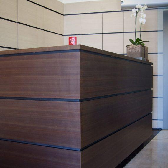 Bancone reception con boiseire in laminato rovere e rame