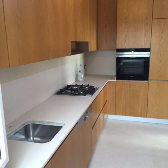 Cucina angolare impiallacciata legno con piano in Silestone